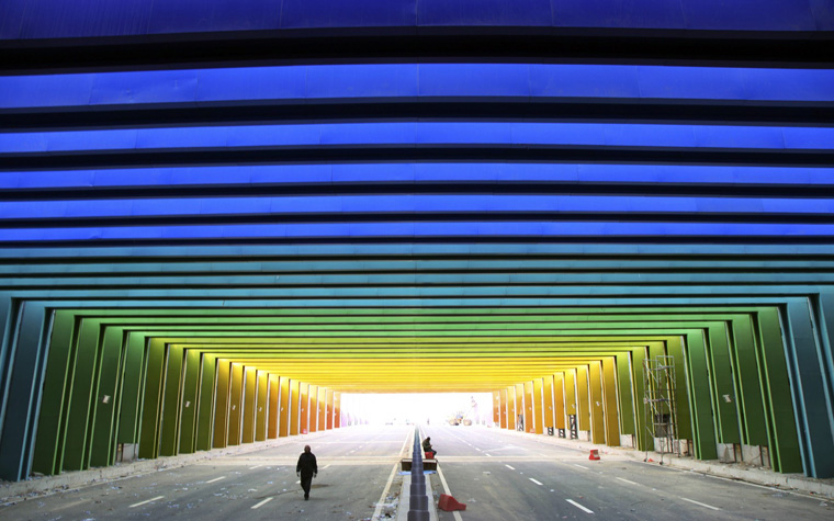 A man walks along a newly-built tunnel, consisting of rainbow colours, in Zhengzhou