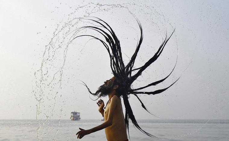 A Sadhu takes a dip at the confluence of the river Ganges and the Bay of Bengal