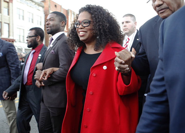 "Oprah Winfrey, producer and cast member of the movie ""Selma"", locks arms with actor David Oyelowo as they participate in a march in Selma, Alabama"