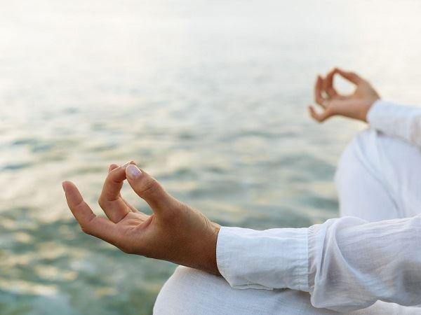 Woman practicing yoga at sunrise near the ocean