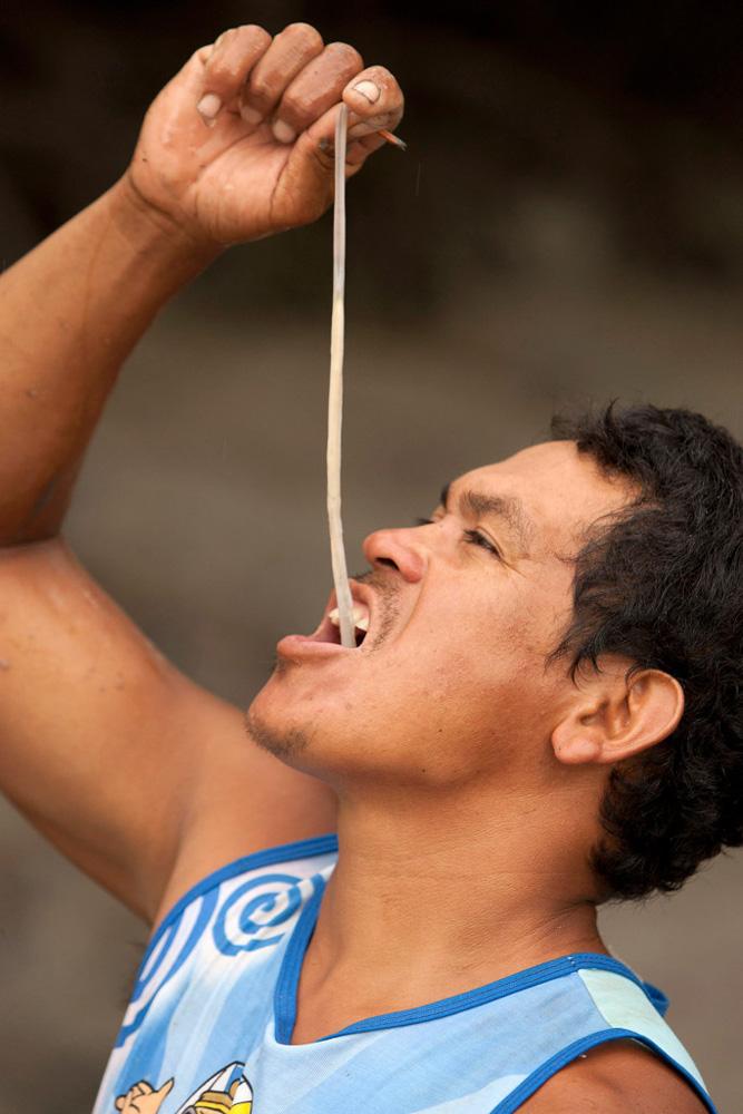 Brazilian fisherman Jose Alfredo de Souza Costa swallows a live shipworm near Curuca
